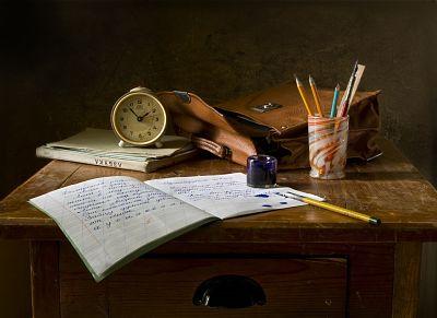 Aparece un pupitre con material escolar: un cuaderno, tintero, varias plumas, libros de texto, una cartera y un reloj.