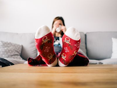 Chica sentada en el sofá con los pies encima de la mesa, una pose que asociamos a menudo a la pereza.