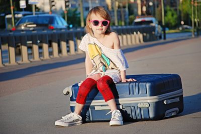 Niña con gafas de sol sentada encima de su maleta de viaje.